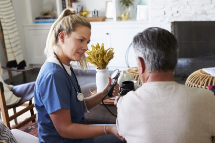 Back view of female healthcare worker measuring the blood pressure of senior man during a home visit