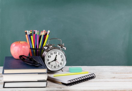 Time for back to school concept including books and stationery supplies with green chalkboard