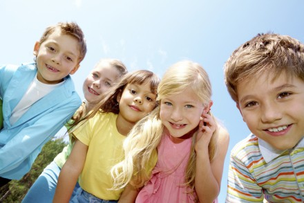 Portrait of smiling children looking at camera on background of blue sky
